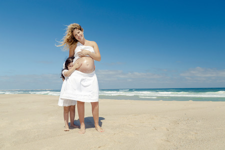 expectant mother: Beautiful pregnant woman in the beach with her little daughter applying sunscreen on moms belly