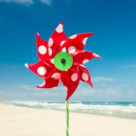 MOLINOS DE VIENTO: Molino de viento rojo con una playa como fondo