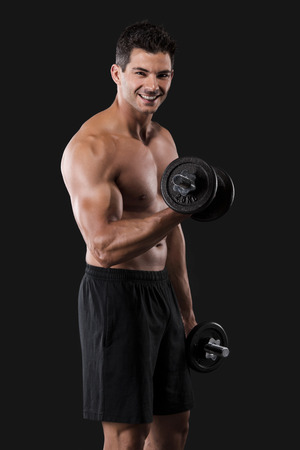 Portrait of a muscular man lifting weights against a dark background Stock Photo - 24841012