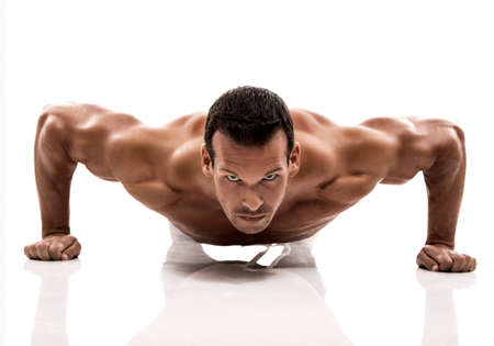 Muscle man dmaking push ups in studio, isolated over a white background photo