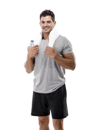 Portrait of a athletic man after doing exercises and holding a bottle of water, isolated over a white background photo
