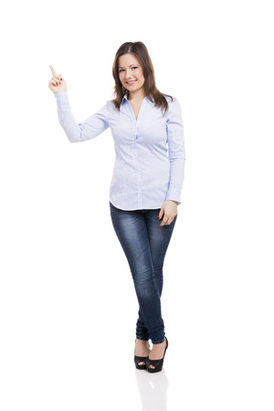 Beautiful woman smiling and pointing to her right side, isolated over a white background photo