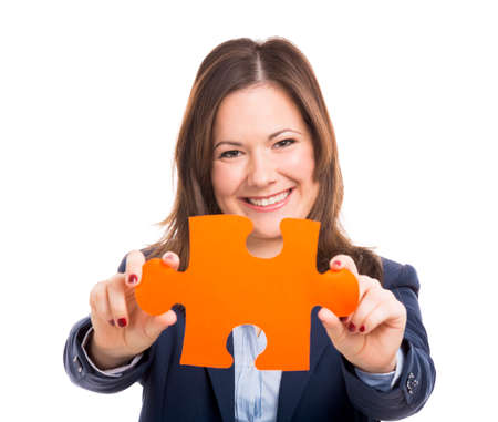 Business woman holding a puzzle piece, isolated over white photo