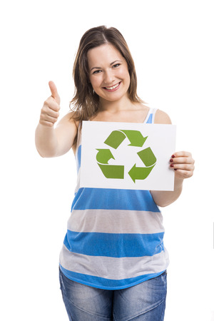 Beautiful young woman holding a paper card with the recycling symbol, isolated over white background photo