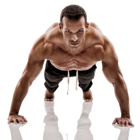 muscle: Muscle man dmaking push ups in studio, isolated over a white background