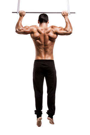 Muscle man in studio making elevations, isolated over a white background photo