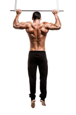 Uomo del muscolo in studio facendo elevazioni, isolato su uno sfondo bianco
