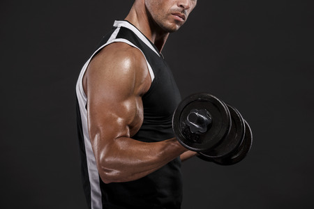 Muscle man in studio lifting weights, isolated over a white background photo