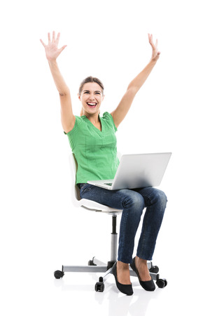 latin girls: Beautiful and happy female student sitting on a chair with a laptop and arms up, isolated over a white background