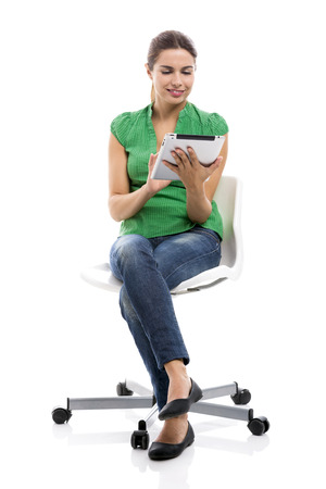 Beautiful female student sitting on a chair with a tablet, isolated over a white background photo