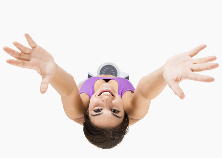 Weight Scale: Top view of a beautiful athletic woman with arms up, isolated on white Stock Photo