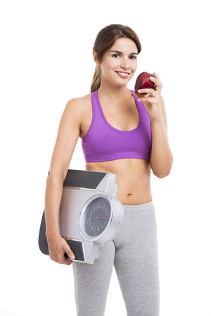 Beautiful athletic woman eating an apple and holding a scale, isolated on white photo