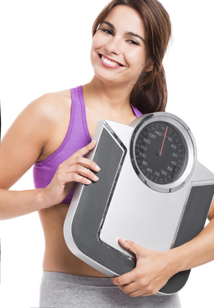 Beautiful athletic woman smilling and holding a scale, isolated on white photo