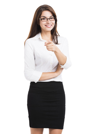 secretary skirt: Beautiful hispanic business woman smiling with and pointing, over a white background