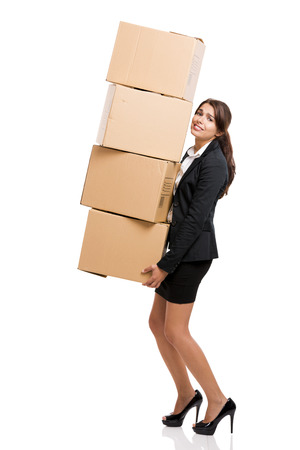 heavy lifting: Business woman carrying card boxes, isolated over white background