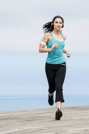 Beautiful young woman jogging on a boardwalk and listen music Standard-Bild
