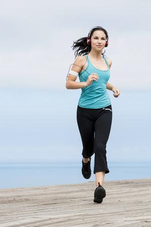 Bella giovane donna jogging su un lungomare e ascoltare musica