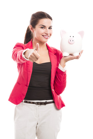 Business woman holding a piggy bank and doing thumbs up, isolated over a white background photo