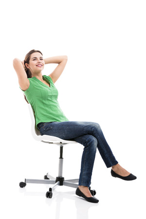 Beautiful student sitting on a chair, isolated over a white background photo