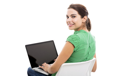Beautiful female student sitting on a chair with a laptop, isolated over a white background photo