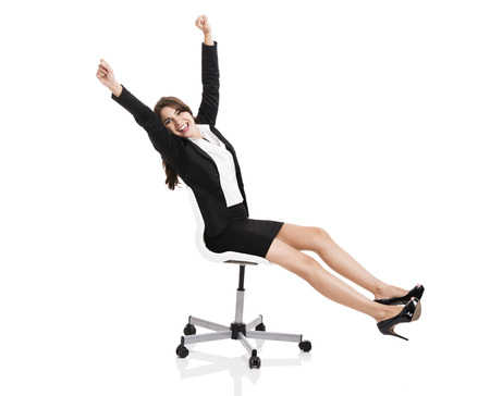 Happy business woman sitting on chair with arms up, isolated over white background photo