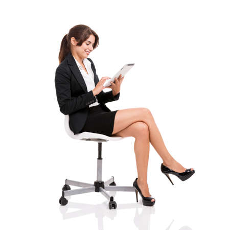 Happy business woman sitting on chair working with a tablet, isolated over white background photo