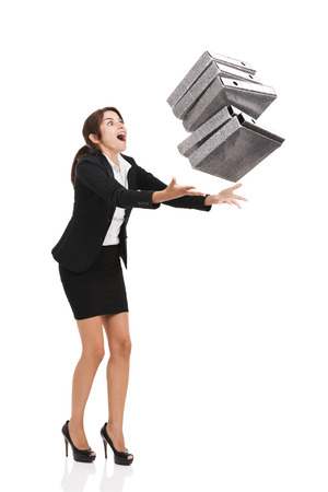 to stumble: Beautiful business woman stumble while carrying lots of folders on hands, isolated over white background
