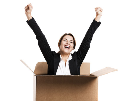 Happy business woman appear inside a big card box, isolated over white background photo