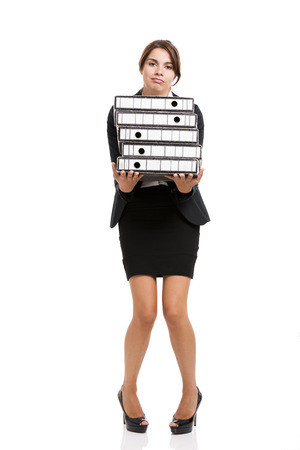 Beautiful business woman tired of work and carrying lots of folders on hands, isolated over white background photo
