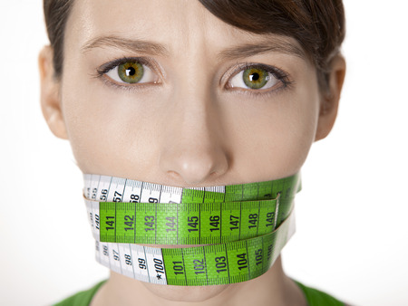 Portrait of a young  woman with a green measuring tape covering the mouth Stock Photo