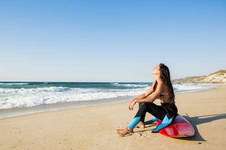 surf girl: A beuatiful surfer girl making preparation for a surf session