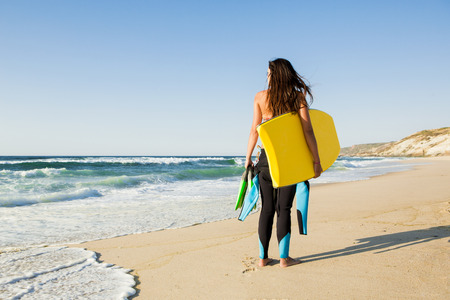 back exercise: A beautiful girl at the beach with her bodyboard