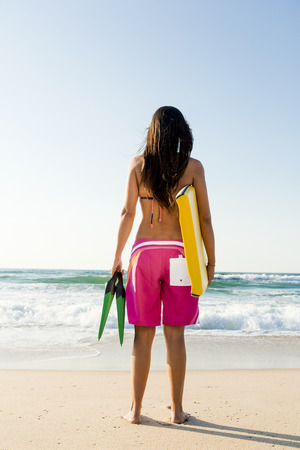 A beautiful girl at the beach with her bodyboard photo