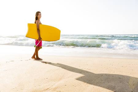 bodyboard: A beautiful girl at the beach with her bodyboard