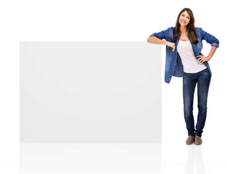 Beautiful woman standing over a blank billboard, isolated over a white background photo