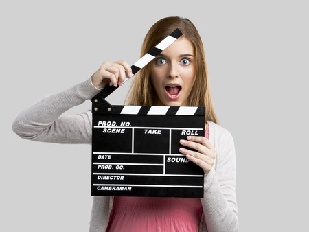 Beautiful blonde woman holding  a clapboard, isolated over gray background photo
