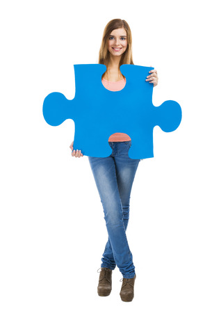 Beautiful blonde woman holding a blue piece of puzzle photo