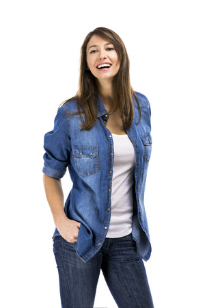 Beautiful woman standing over a white background with hands on the pockets and smiling photo