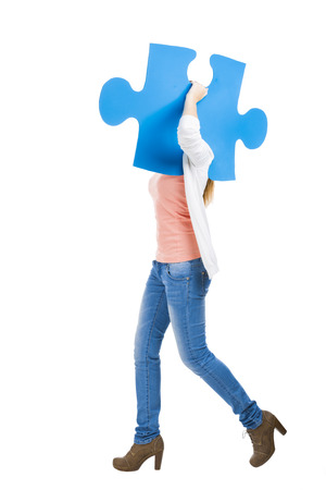 Beautiful blonde woman holding a blue piece of puzzle while walking photo