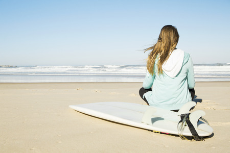 Teenage surfer girl sitting in the beach and checking the waves photo