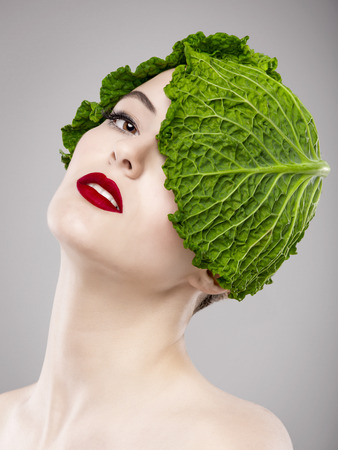 Portrait of a woman illustrating a vegan concept with a cabbage on the head photo