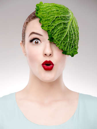 admired: Portrait of a woman illustrating a vegan concept with a cabbage on the head