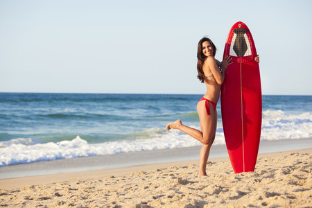 A beautiful surfer girl at the beach holding up her surfboard photo
