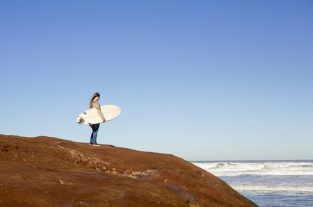 surf girl: Teenage girl over the rocks checking the waves