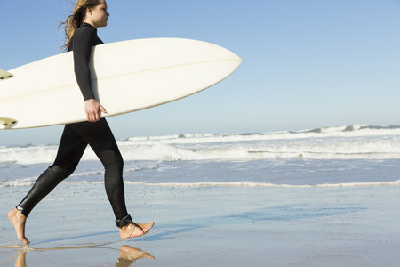 surf girl: Teenage girl walking on the beach with her surfboard Stock Photo