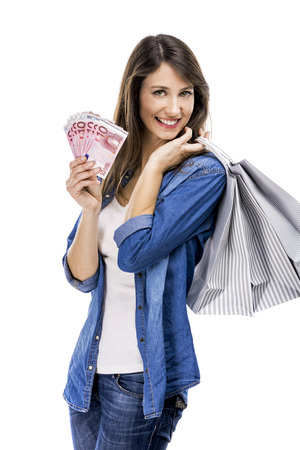 Beauitful woman holding shopping bags and some Euro currency notes, isolated over white background photo