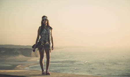 Beautiful and fashion young woman posing at the sunset with a skateboard photo