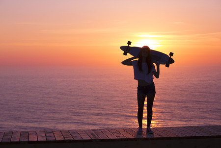 Beautiful girl holding a skateboard with the sunset in the background photo
