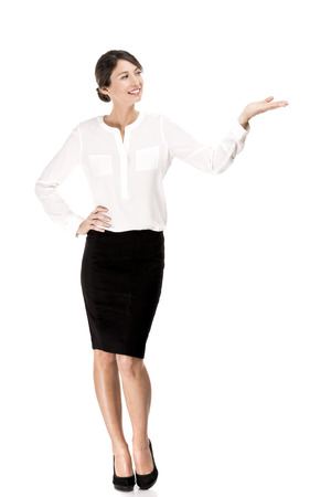 Business woman showing something with her hand, isolated over a white background photo