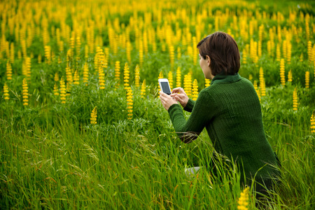 Woman taking pictures to flowers with a cellphone Stock Photo - 27647132
